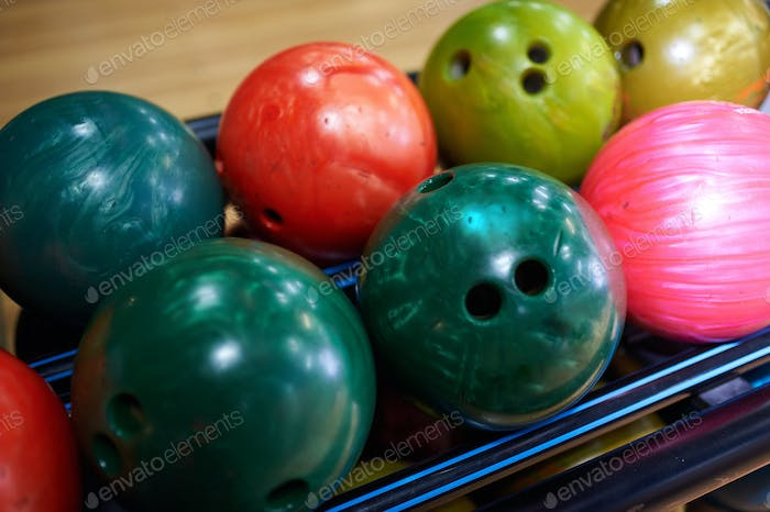 Stand with colorful bowling balls in club
