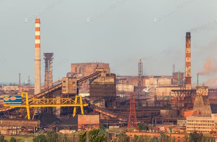 Stahlfabrik mit Rauchstapel bei Sonnenuntergang