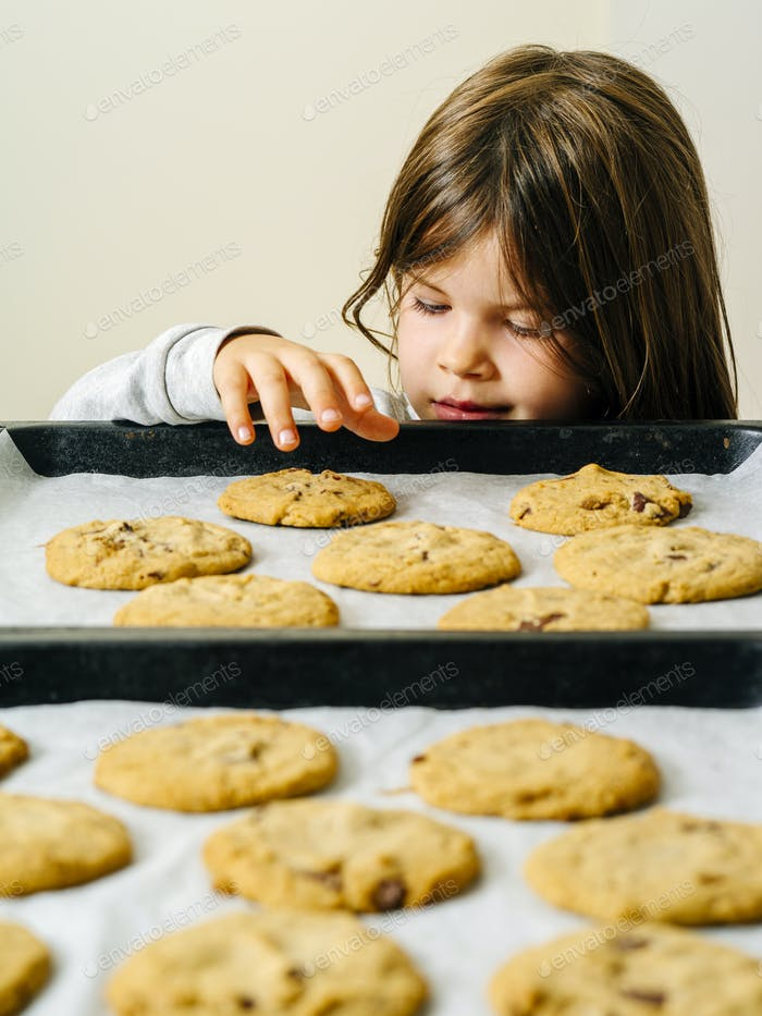Young girl grabbing cookies from a baking tray