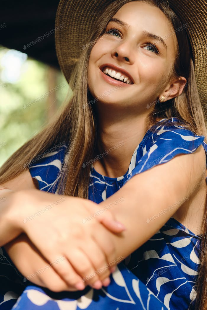 Portrait of beautiful cheerful girl in blue dress and hat happily sitting in city park
