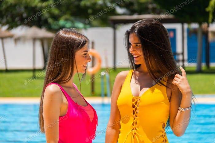 two teenagers in swimsuits in a hotel pool posing and smiling