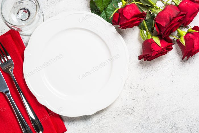 Romantic holiday table setting with plate, roses and present