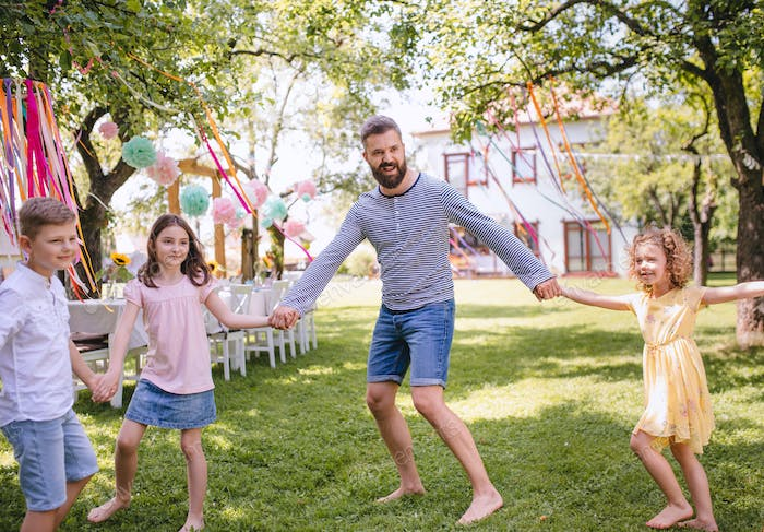 Man with kids on birthday party playing outdoors in garden in summer