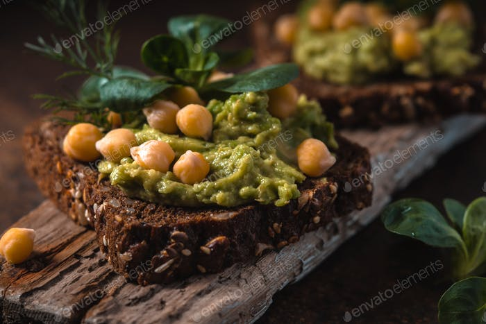 Open sandwich with avocado cream and greens  on the wooden board