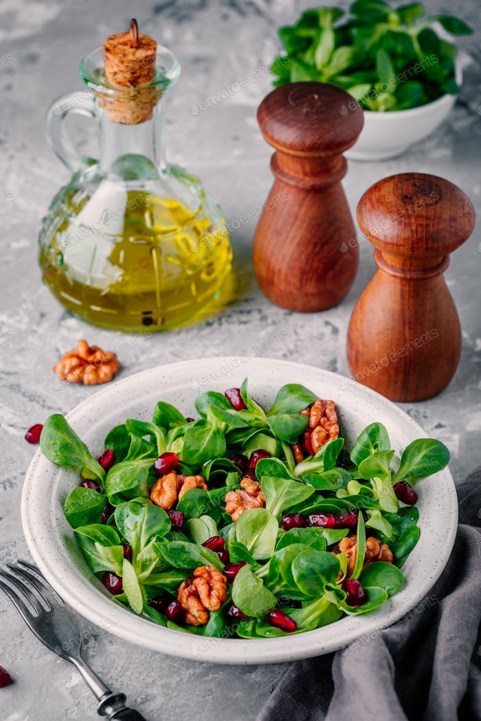 Healthy green Lamb's lettuce salad with walnuts and pomegranate seeds
