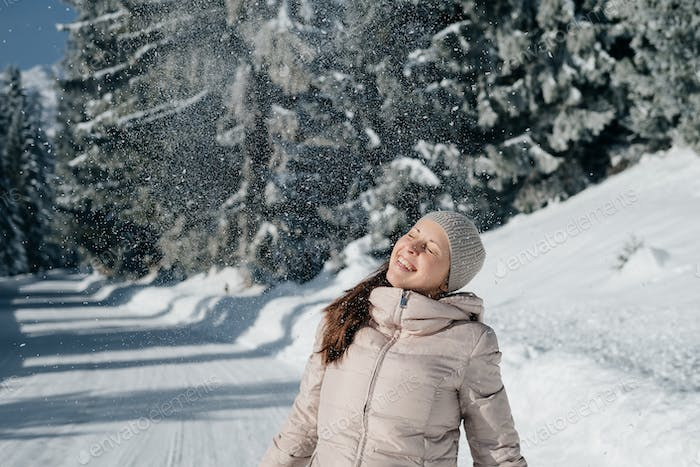Happy  young woman  having funwith snow, outdoors.