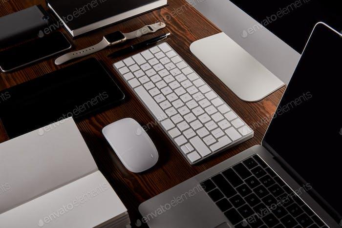 moderner Arbeitsplatz mit verschiedenen Geräten auf Holztisch