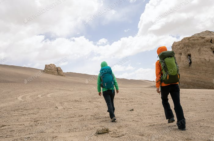 Two women hikers hiking on sand desert