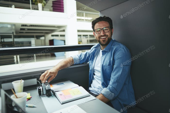 Laughing designer working inside of an office meeting pod