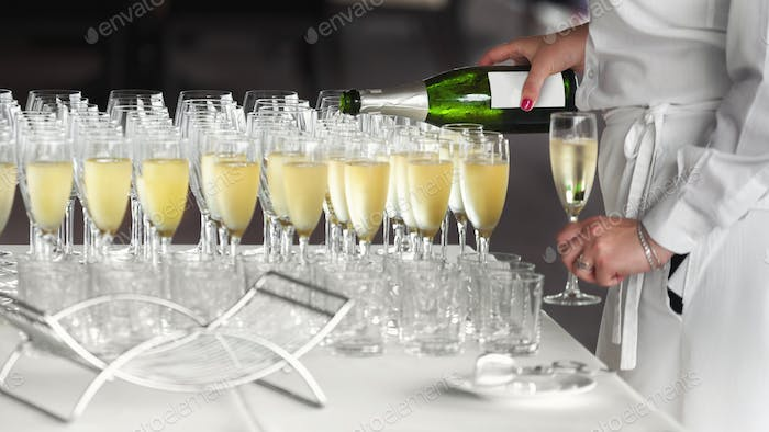Female waiter pouring cold champagne in glasses