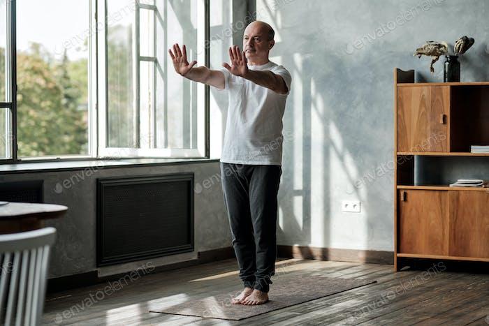 Hispanic man working out, yoga in basic standing asana tadasana