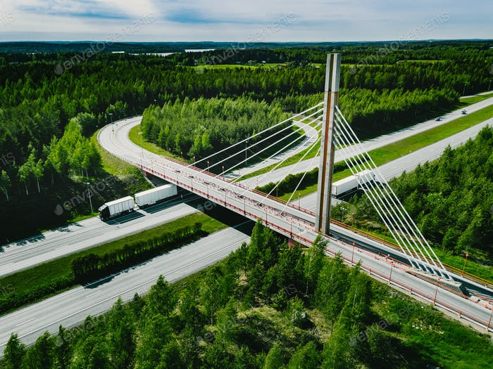 Aerial top view of cable-stayed Suspension bridge and Highway road with green forests in Finland.