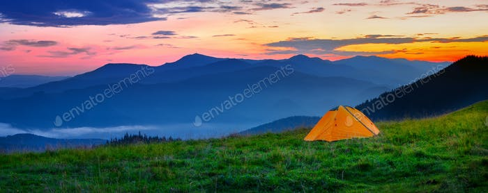 Orange tent in the mountains at sunset