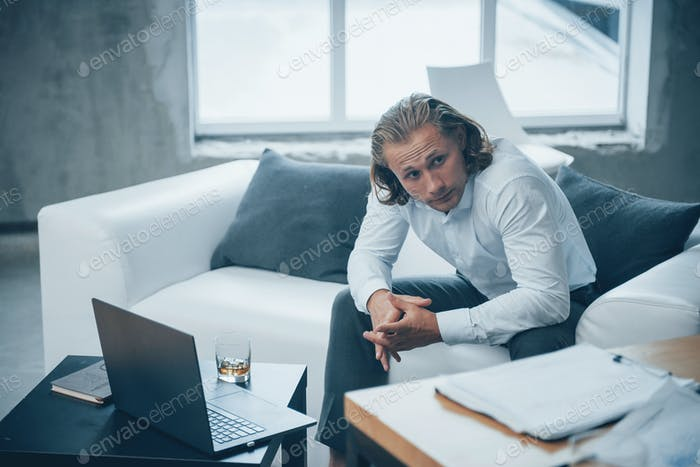 Exhausted guy in the classic wear feels stressed