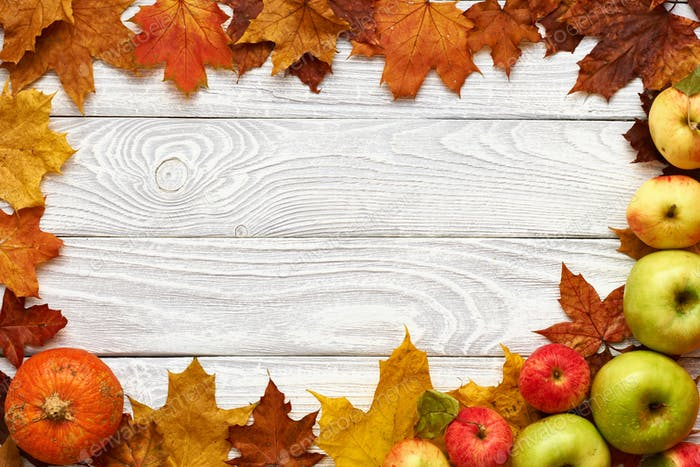 Autumn leaves, apples and pumpkin over wooden background