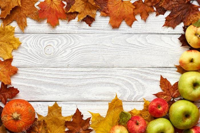 Herbstblätter, Äpfel und Kürbis über Holzhintergrund