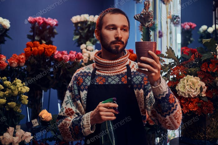 Portrait of young florist with cactus