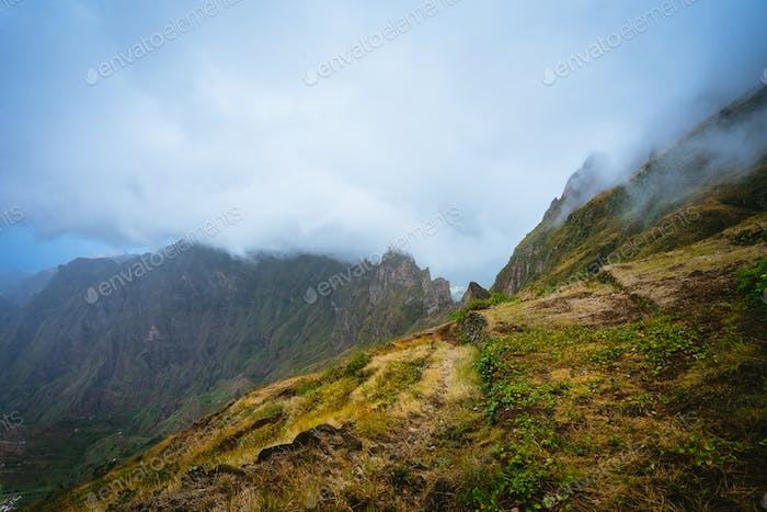 Trekking path beside the mountain peak chain overgrown with verdant grass and cultivated plants