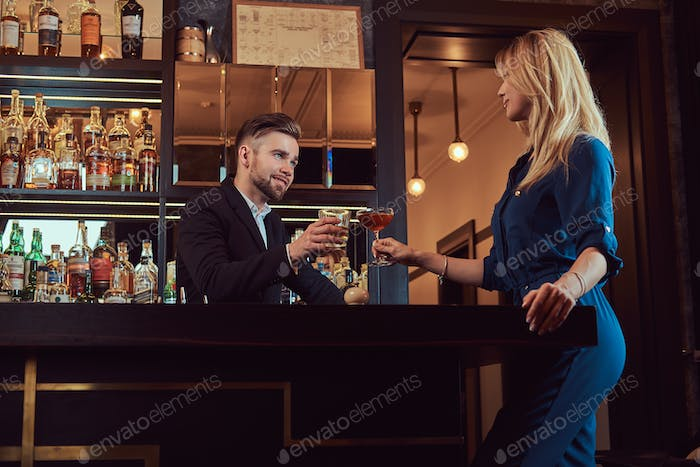Stylish couple is spending the evening in a romantic setting, drinking wine at the bar counter.