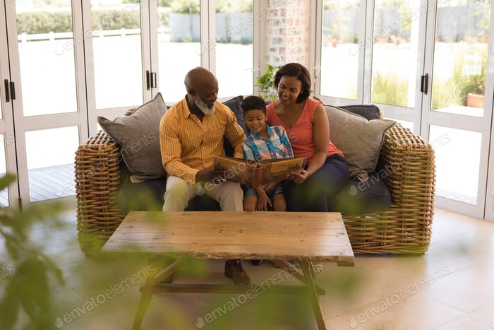 Family reading story book in living room at home