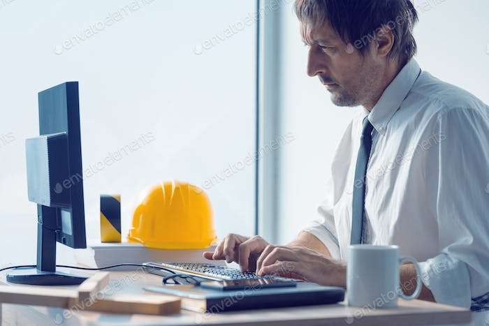 Construction engineer working on desktop computer using CAD soft