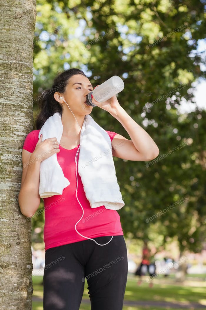 Sporty woman leaning against a tree and drinking while having a break
