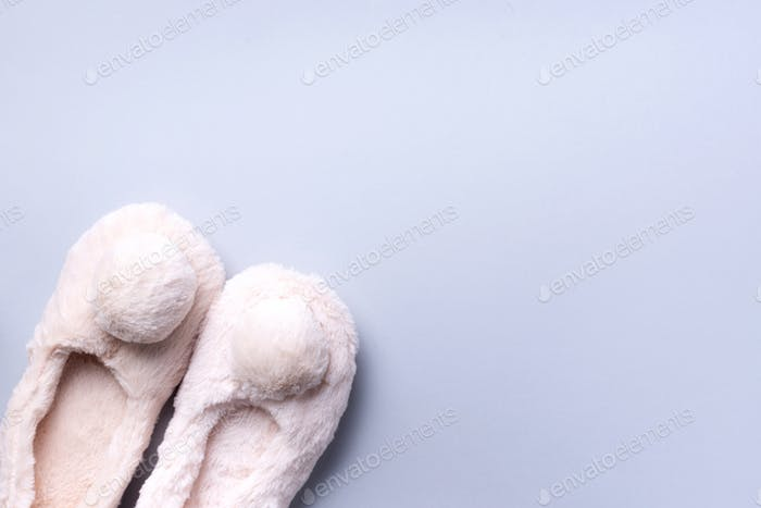 Nude fluffy home slippers with pompon on pastel grey background. Top view. Copy space. Cozy home