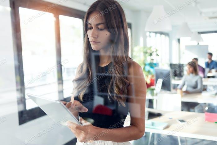 concentrada joven empresaria usando su tableta digital