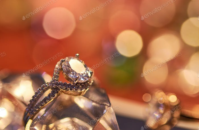 Close-up view of engagement ring with colorful background