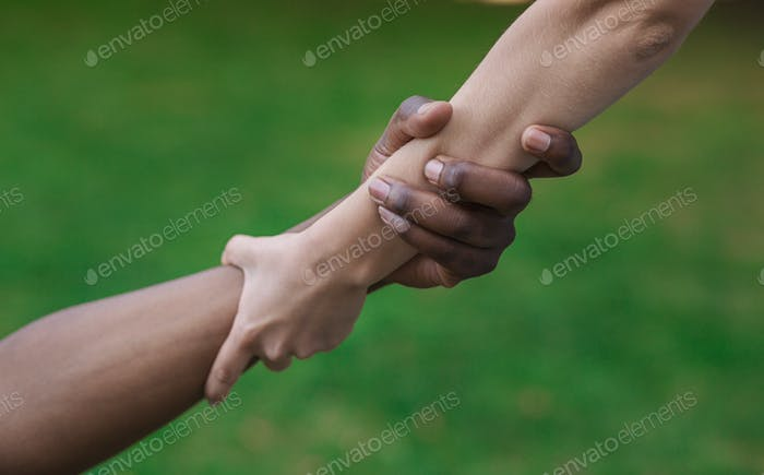 Multiethnic friends helping hand outdoor, copy space