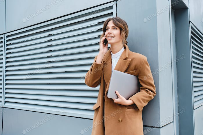 Young pretty businesswoman in coat with laptop happily talking on cellphone outdoor
