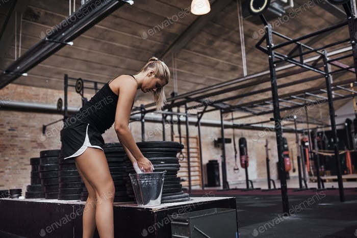 Fit young woman chalking her hands before a gym workout