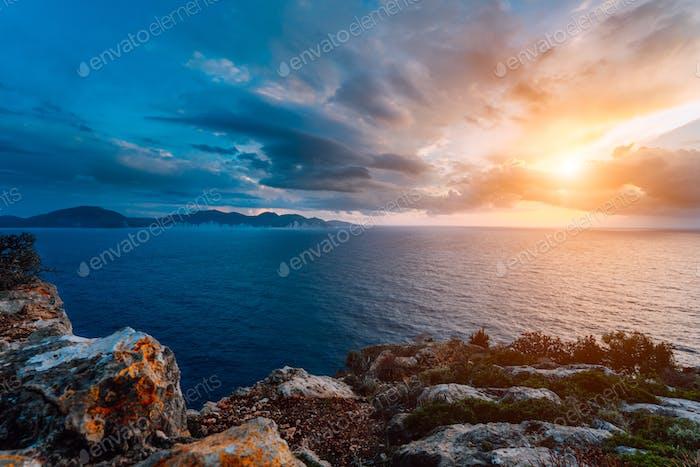 Dramatic sunset on the coastline. Motion clouds on horizon, rainy weather