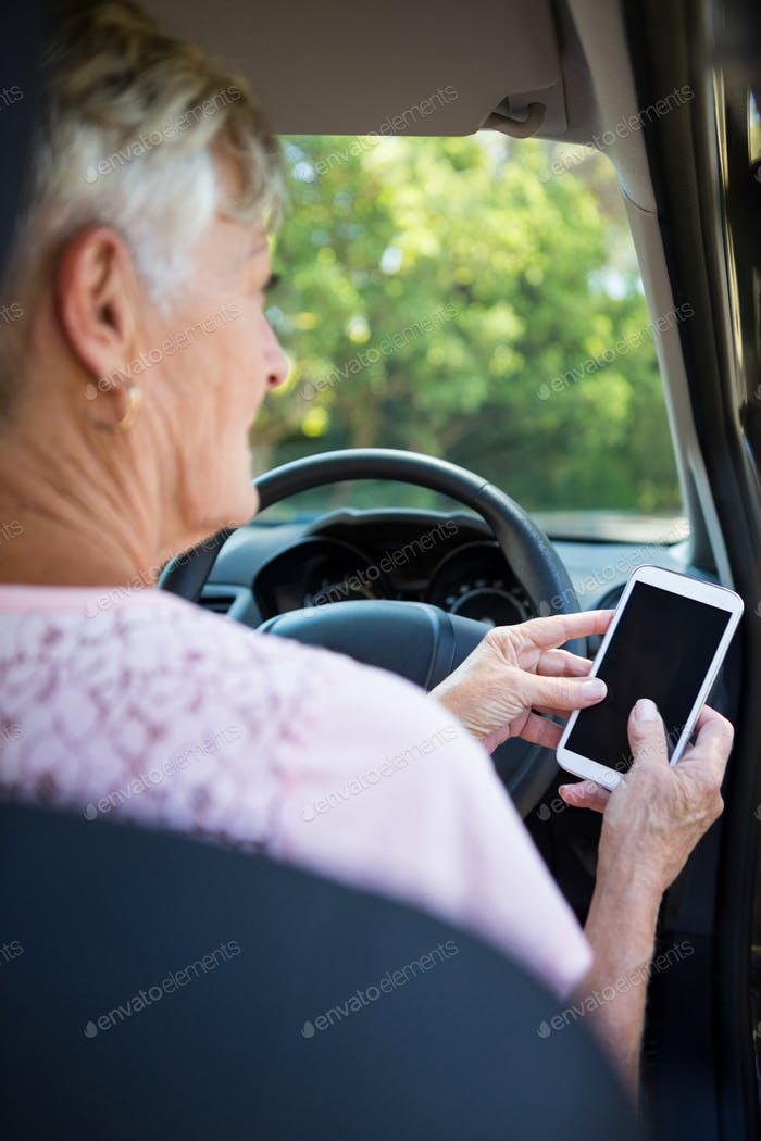 Senior woman using mobile phone while driving a car