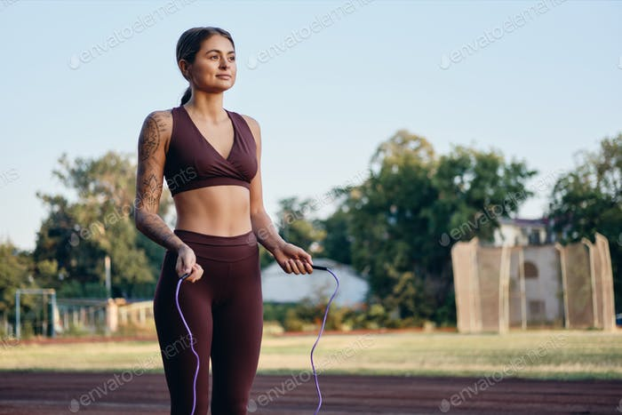 Beautiful fitness girl in stylish sportswear with skipping rope dreamily training on city stadium