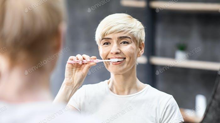 Lächelnde Dame Reinigung Zähne mit Zahnbürste Im Bad, Panorama
