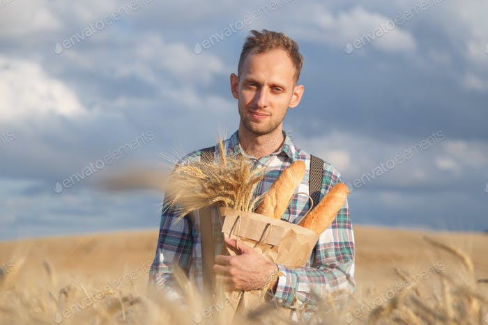 Male farmer or baker with baguettes in rye, wheat field