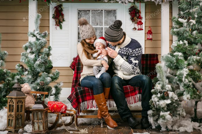 Young family with a baby boy sitting on the bench in winter decorations