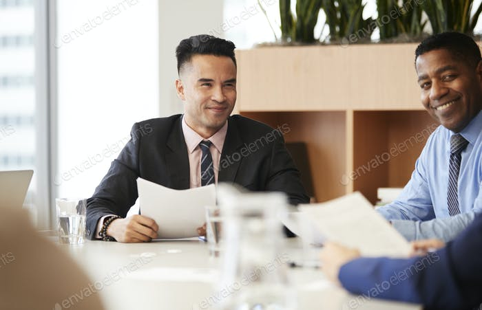 Businessman With Paperwork Sitting At Table Meeting With Colleagues In Modern Office