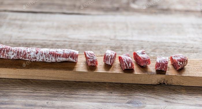 Cut spanish salami on the wooden board