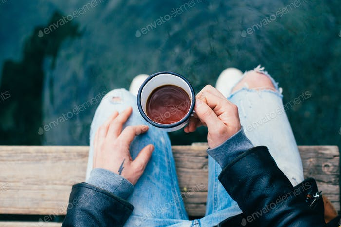 Man drink coffee from enamel cup outdoors