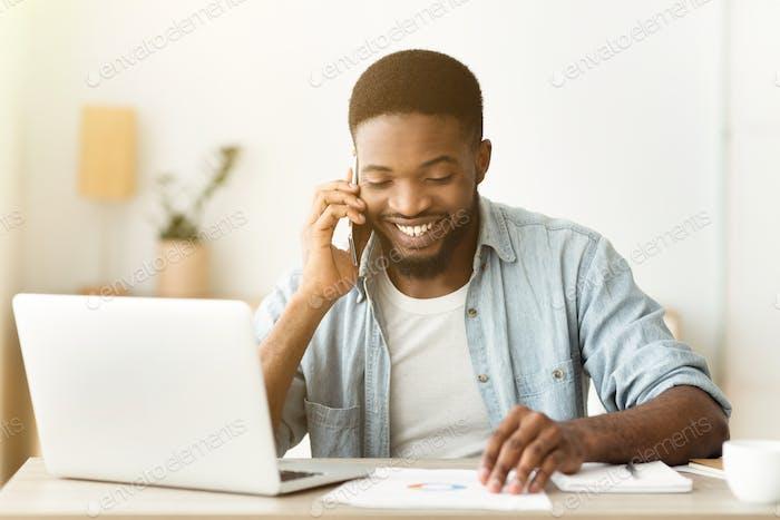 Fröhlicher Afroamerikaner Geschäftsmann telefonisch und lesen Dokumentation