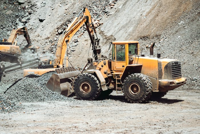 heavy construction machinery in mine - wheel loader transports gravel