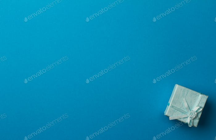Little gift box on light blue background with copyspace