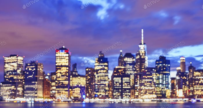 Blurred color toned Manhattan skyline at night, New York.