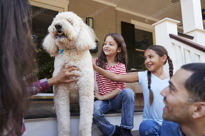 Familie mit Hund sitzend auf Stufen des neuen Hauses auf Umzug In Tag