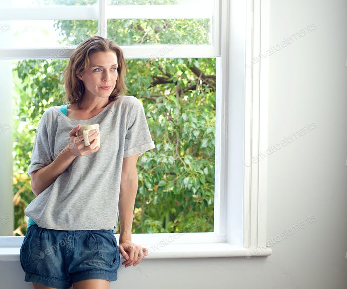 Woman standing by window at home with cup of coffee