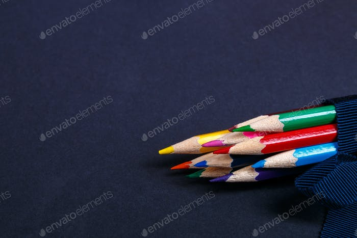 Set of colored pencils wrapped in a blue ribbon on black background. Back to school. Copy space.