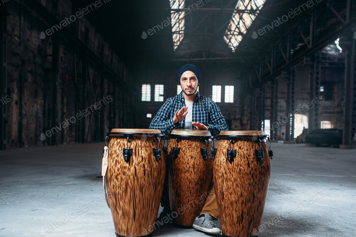 Male drummer plays on wooden drum