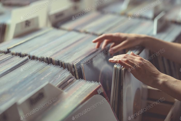 Women's hands browsing records close-up
